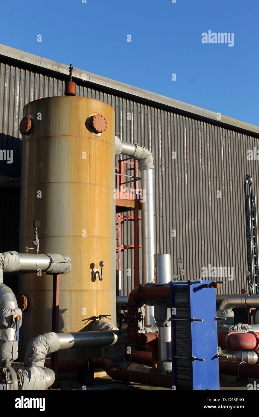 Le réservoir et les tuyaux à l'extérieur du bâtiment industriel. Photo Stock