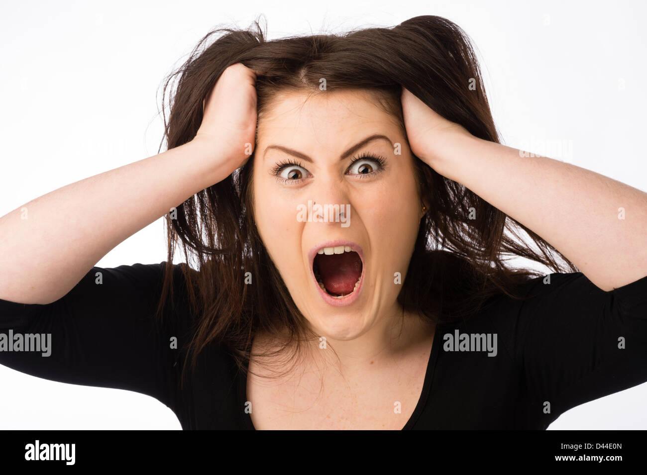 Une jeune femme en colère en criant, arracher en tirant ses cheveux brun , Royaume-Uni Photo Stock
