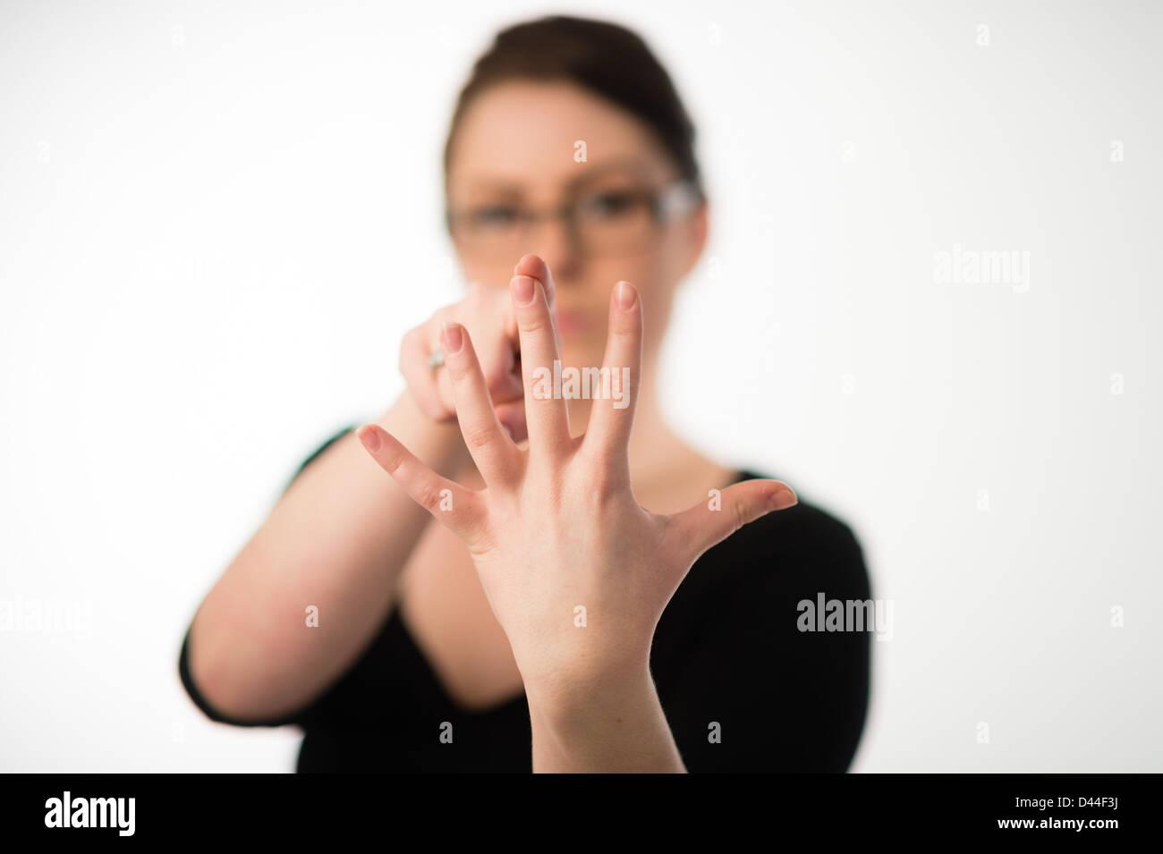 Une jeune femme, les cheveux bruns, compter jusqu'à cinq 5 sur les doigts de sa main, UK Photo Stock