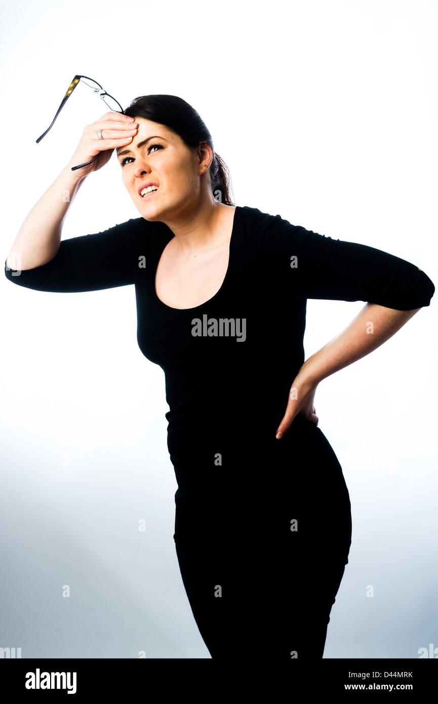Une jeune femme, les cheveux bruns, souffrant de maux de dos, stress tension UK, frottant son dos et la tête Photo Stock