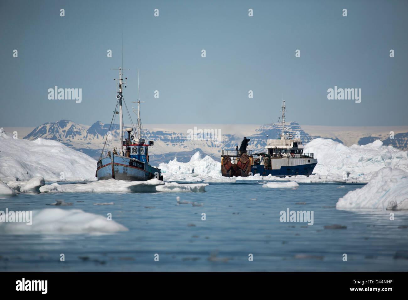 Les bateaux de pêche entre les icebergs au Groenland Photo Stock