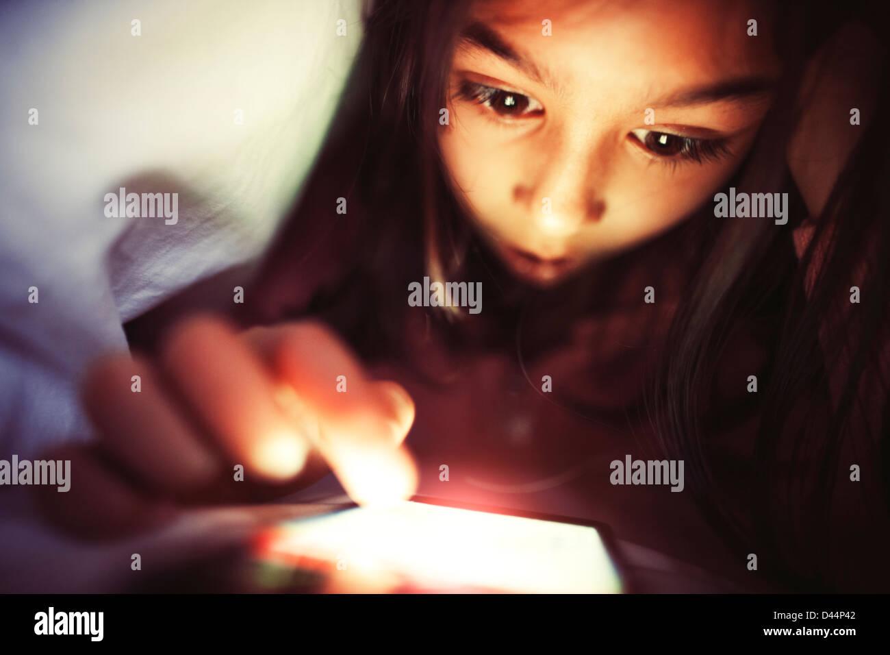 Girl utilise smartphone, sous les couvre-lits Photo Stock