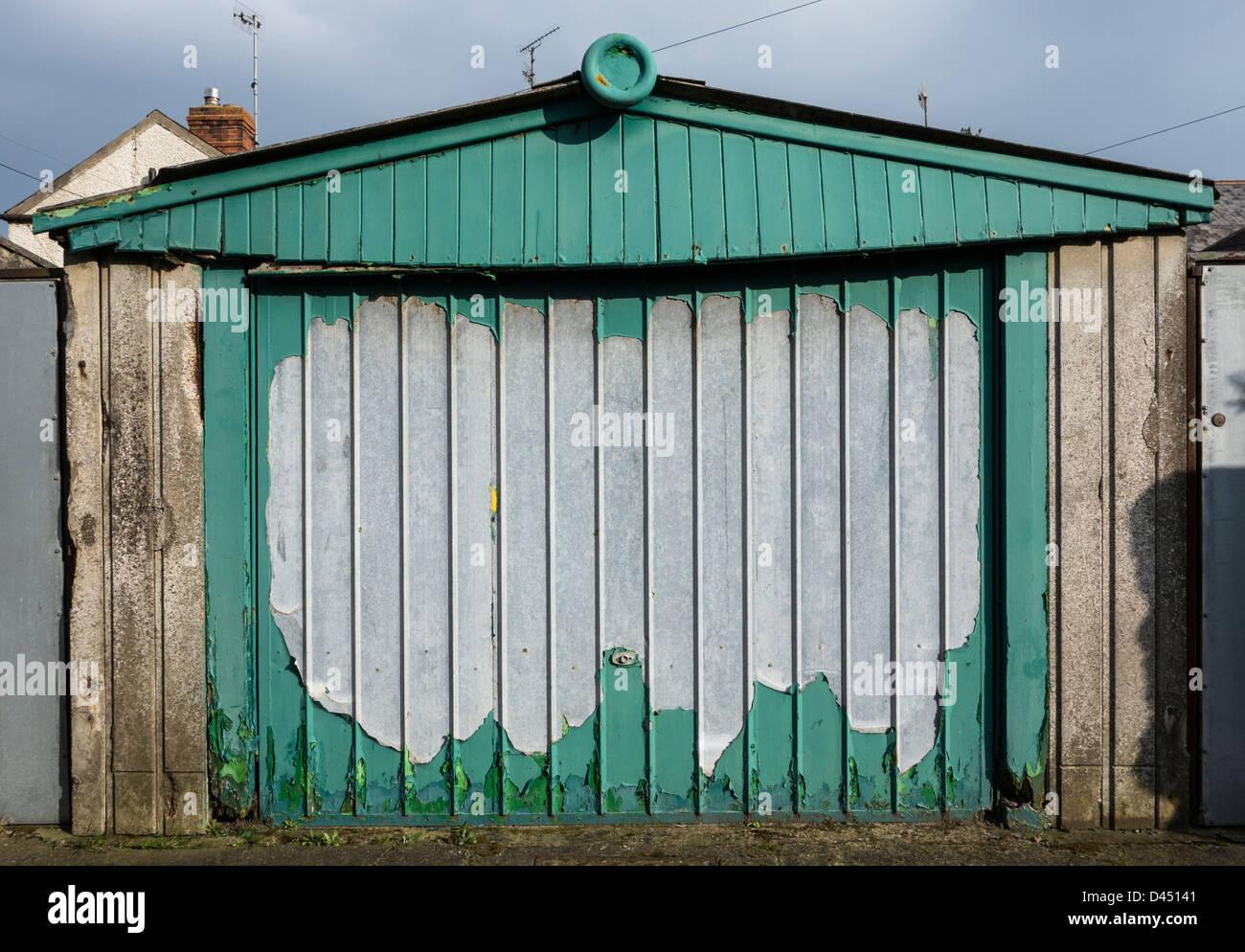 Un affaissement et porte de garage délabré avec de la peinture verte de déroulage Photo Stock