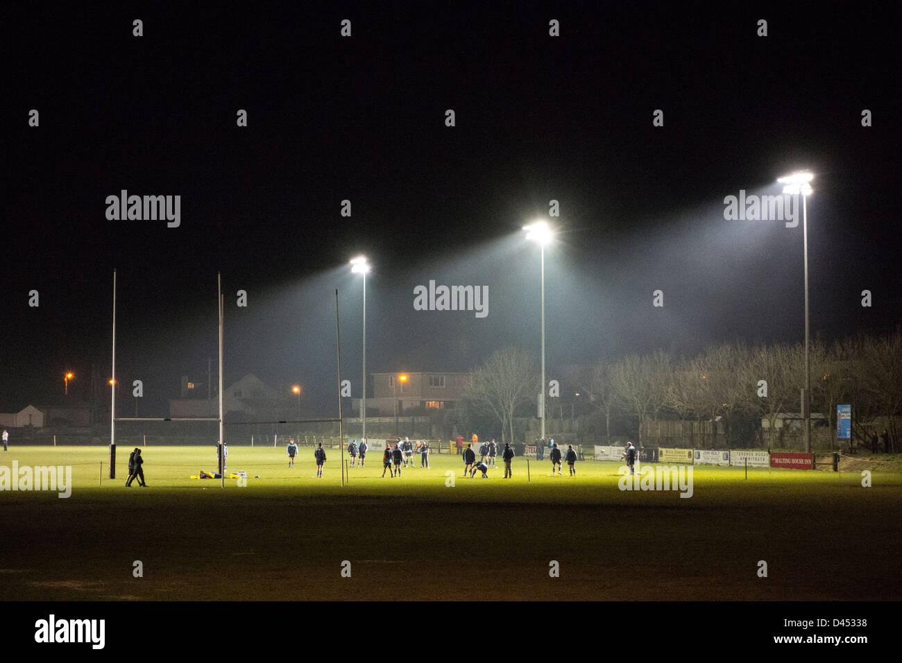 Des joueurs de rugby à exercer sur le terrain la nuit, illuminé par des projecteurs - près de Dublin, Photo Stock