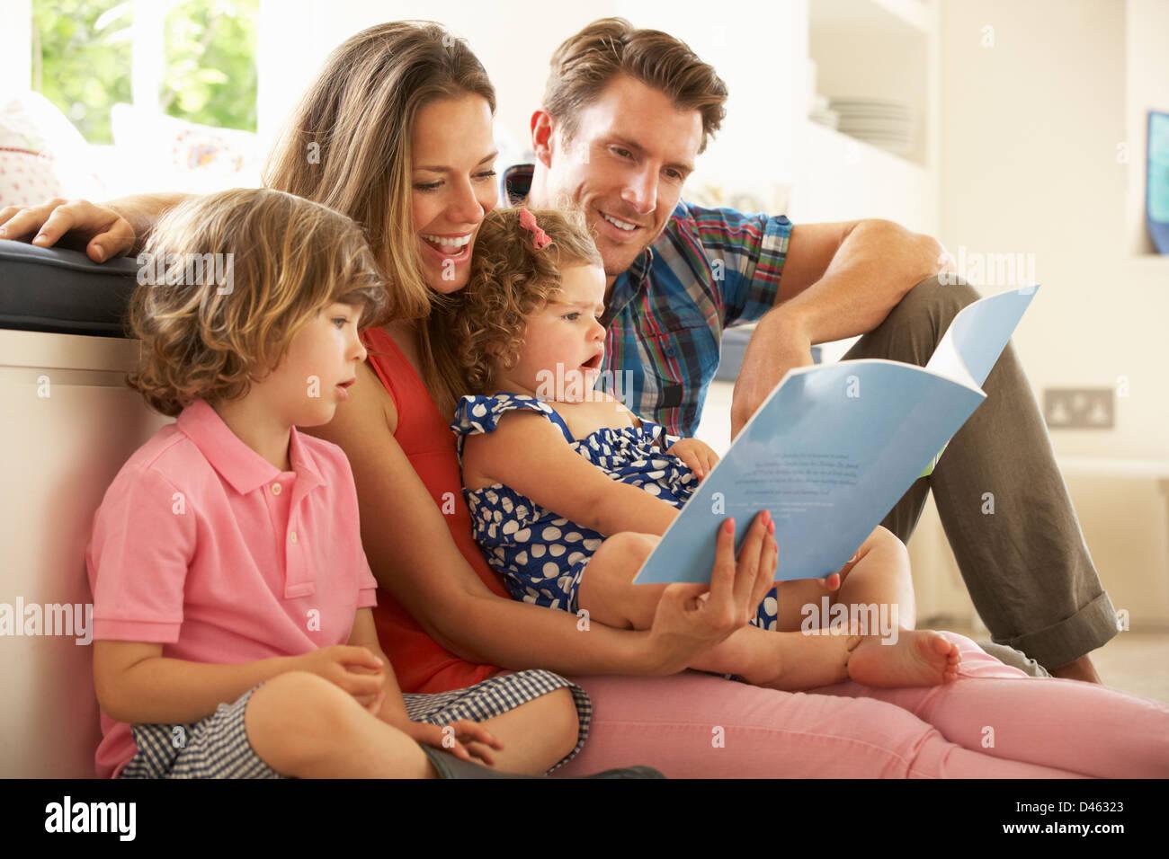 Les parents avec des enfants assis à l'intérieur Histoire de lecture Photo Stock