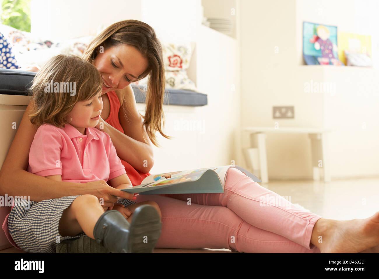 Mère assise avec son histoire de la lecture à l'intérieur Photo Stock