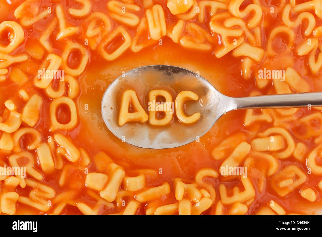 En forme de pâtes lettres ABC sur une cuillère à pâtes en sauce tomate en forme de lettres Photo Stock