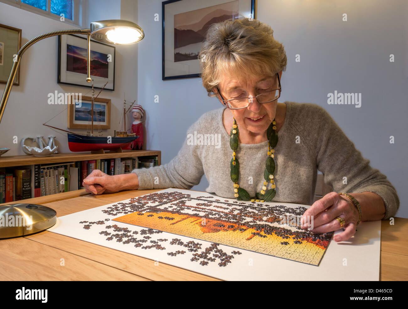Une femme âgée, DAO avec jigsaw à UK Photo Stock
