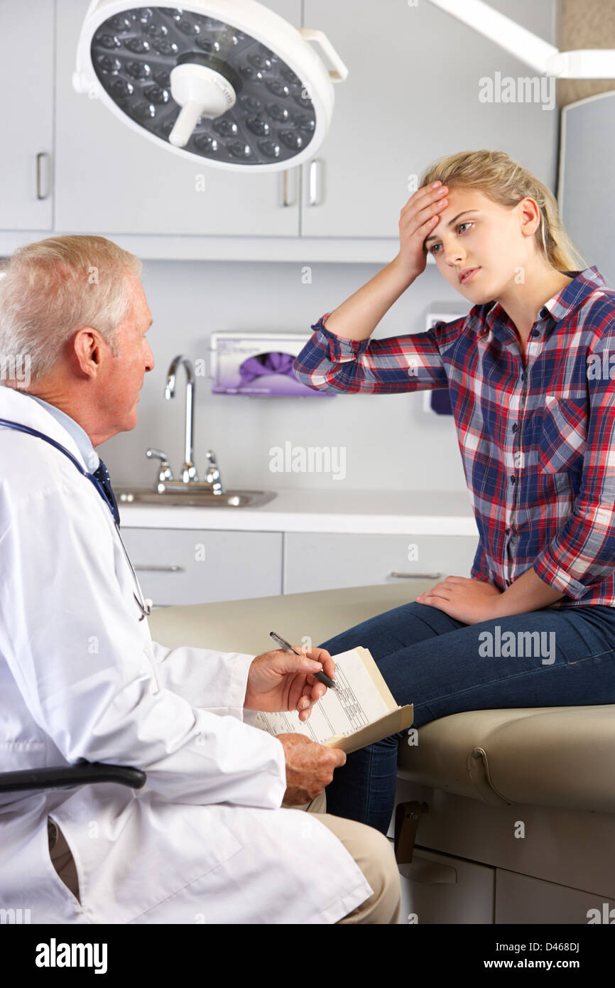Visites adolescente Bureau du médecin avec des maux de tête Photo Stock