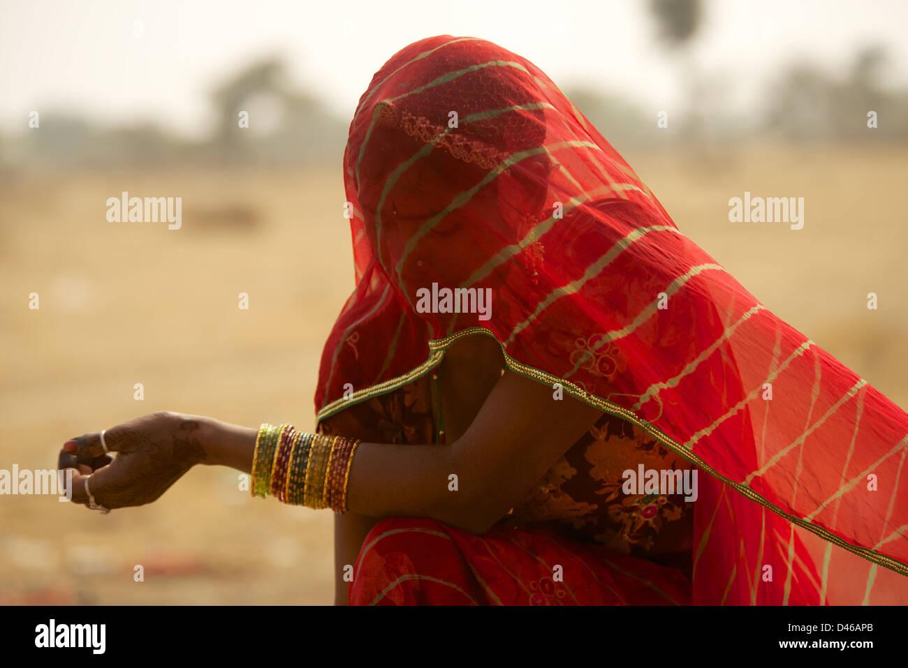 Une jeune femme indienne à la périphérie de Bikaner Rajasthan en Inde du nord. shields son visage Photo Stock