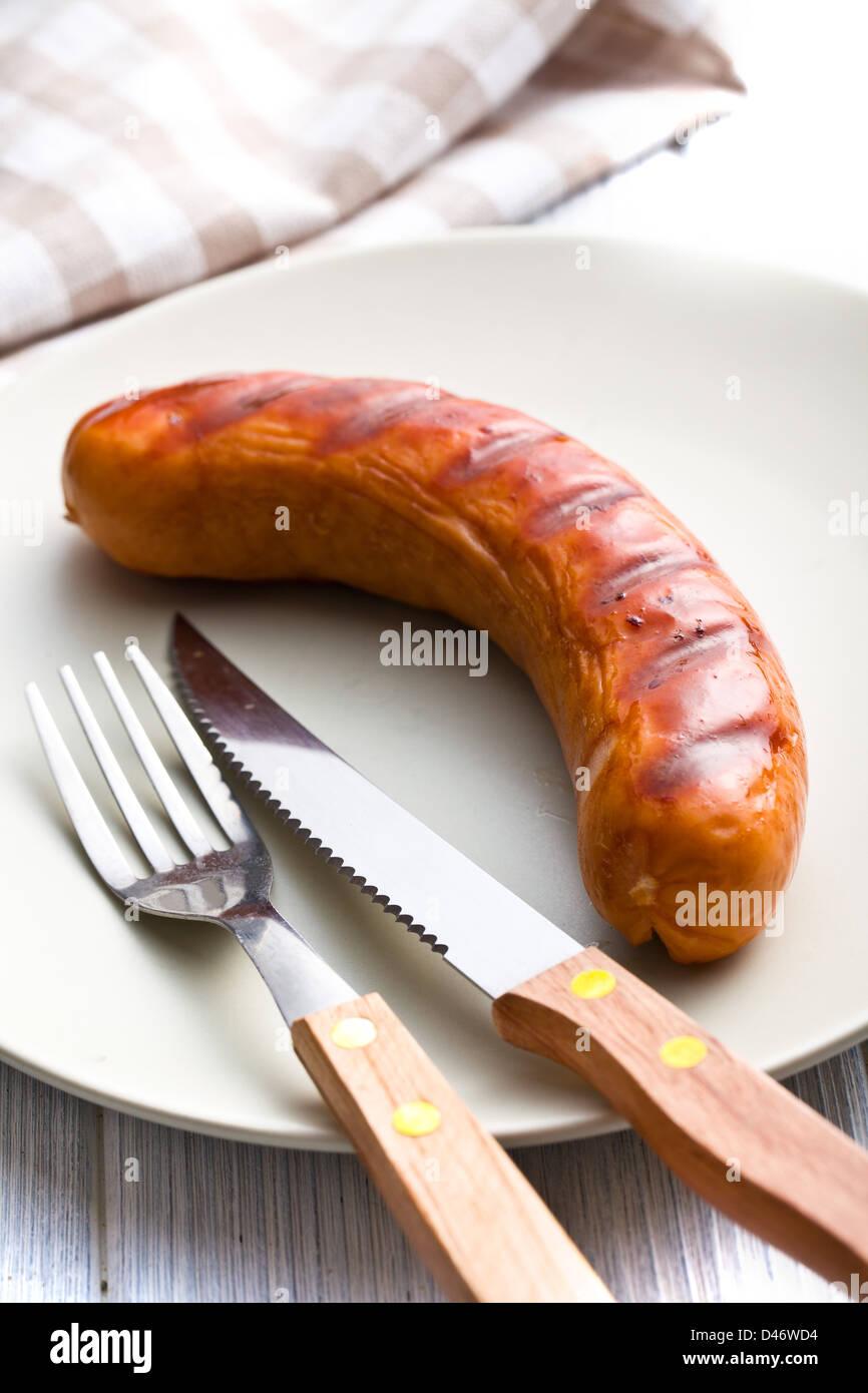 Saucisses grillées sur la plaque avec des couverts Photo Stock
