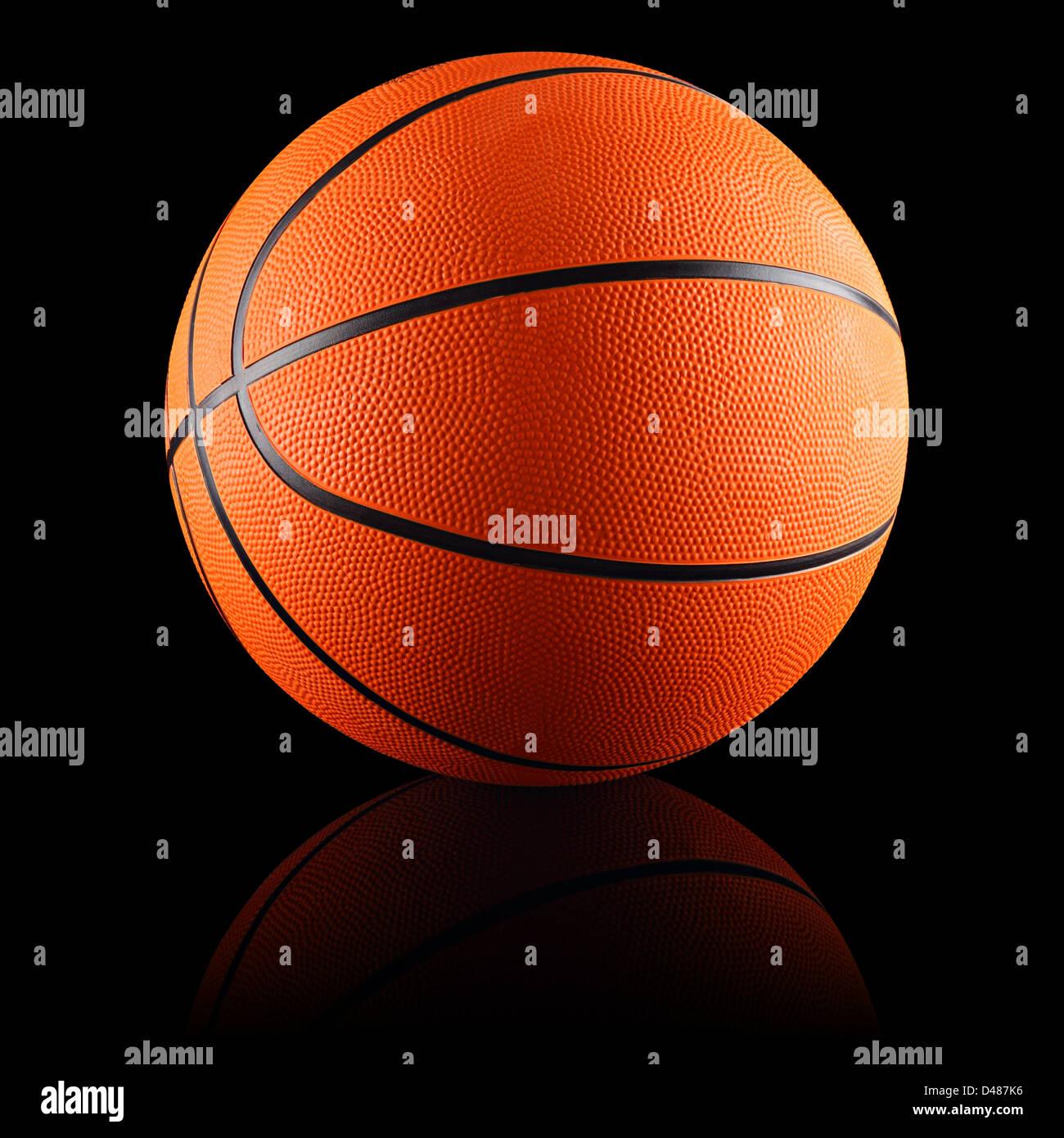 Un terrain de basket-ball orange en face de fond noir Photo Stock
