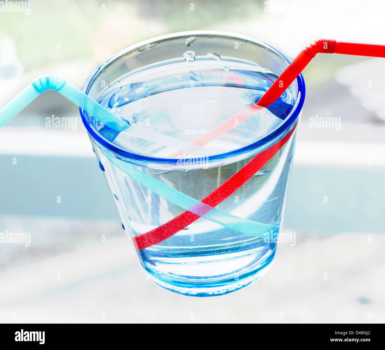Verre avec deux pailles montrant la réfraction dans l'eau Photo Stock
