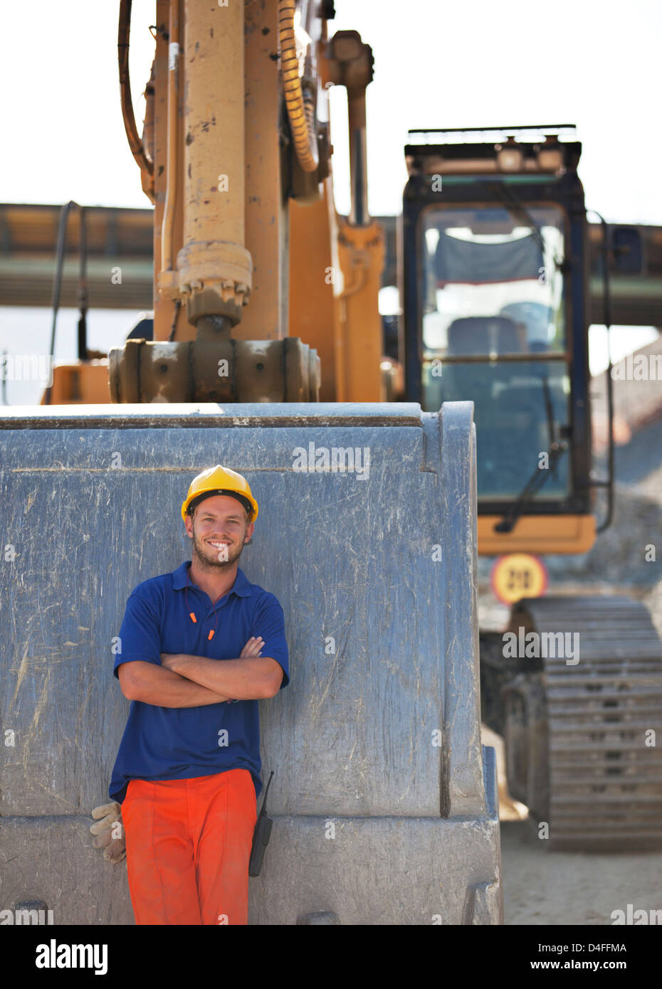 Worker standing by digger sur place Photo Stock