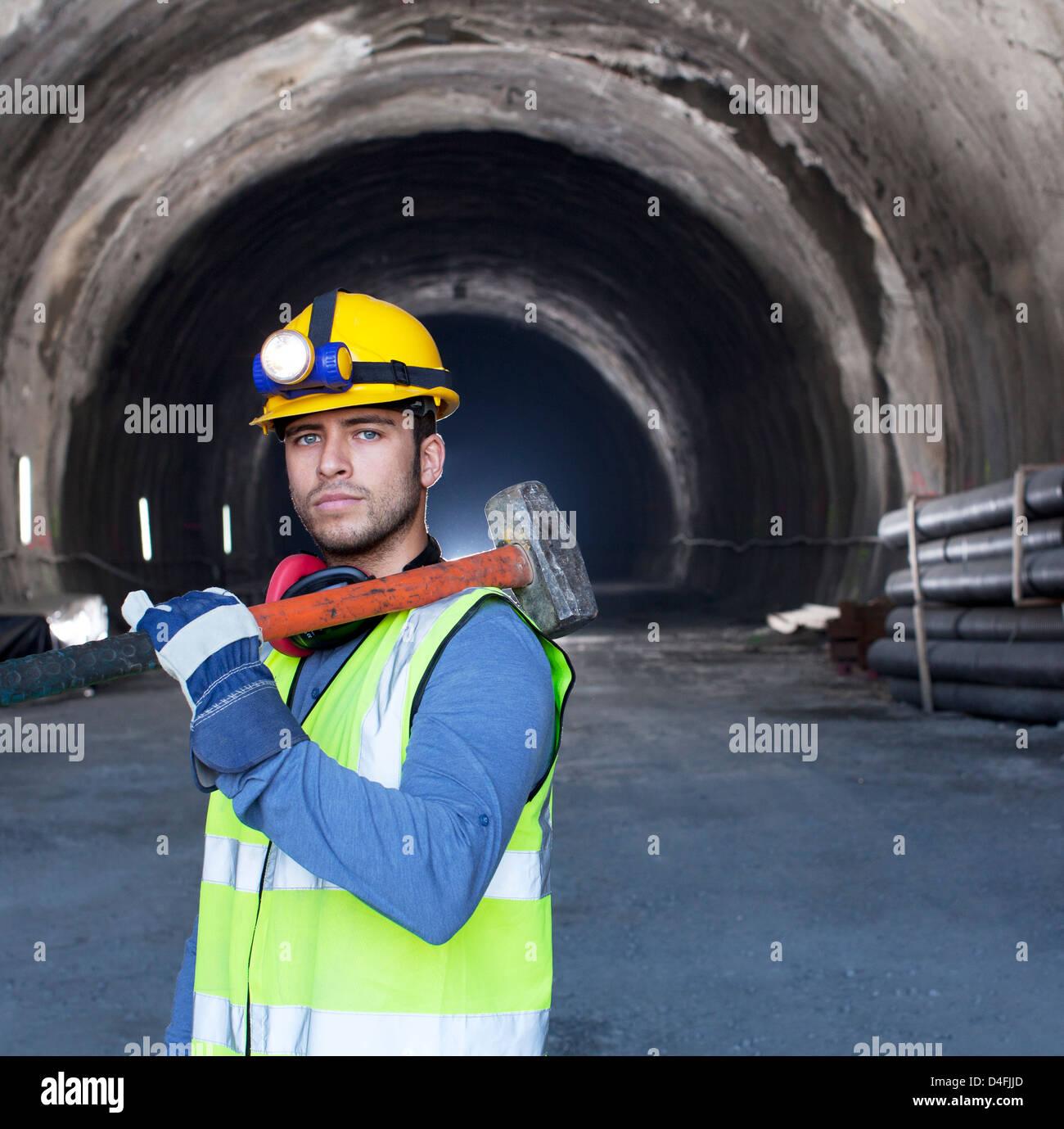Worker holding sledgehammer dans tunnel Photo Stock