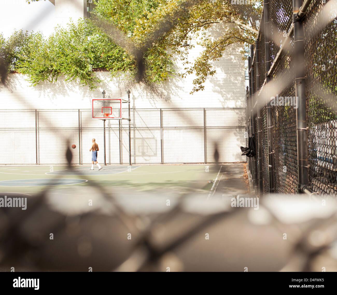 L'homme jouant au basket-ball sur cour urbaine Photo Stock