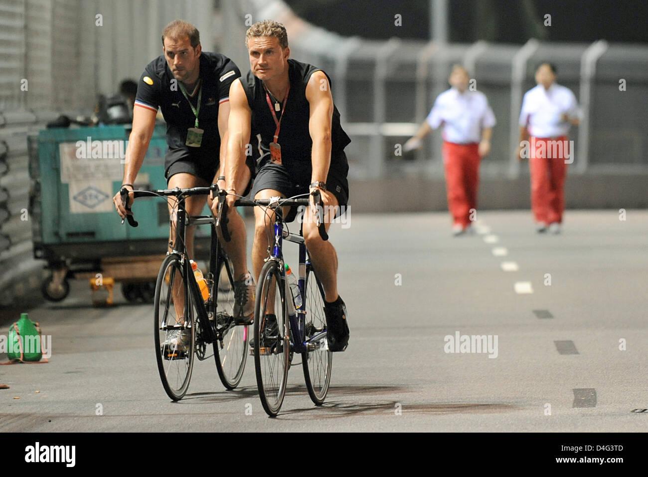 La pilote de Formule 1 David Coulthard (R) de Red Bull avec un vélo sur la piste avant le Grand Prix de Formule Banque D'Images