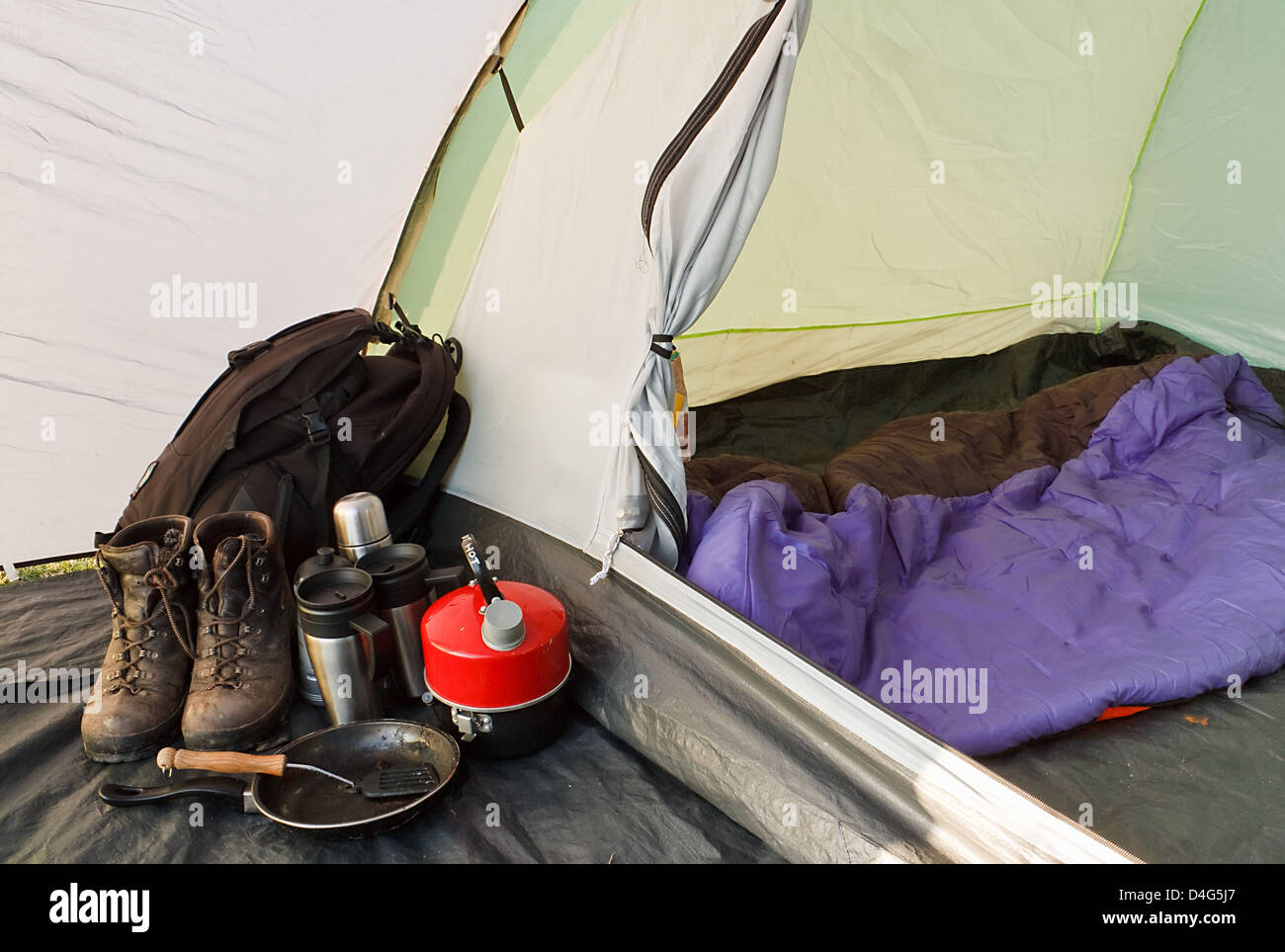 Vue intérieure d'un dôme tente montée pour le camping avec divers équipements et sac de Photo Stock