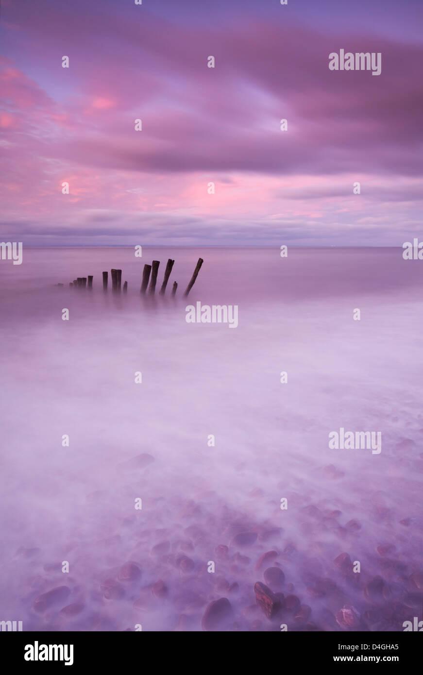 Poteaux de bois à marée haute sur la plage de Porlock, Exmoor, Somerset. Banque D'Images