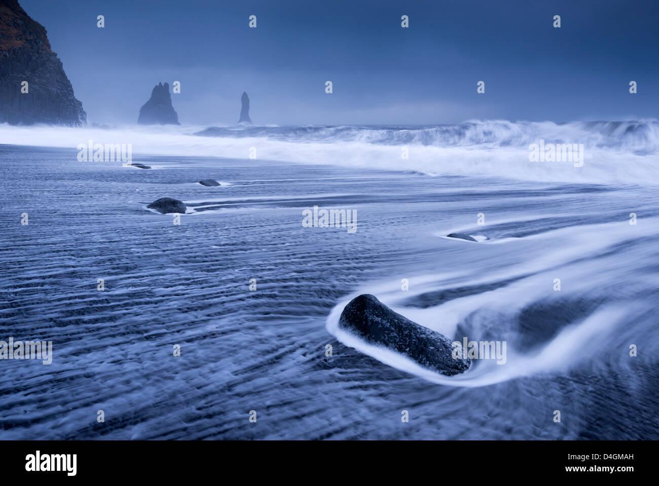 Se précipitant sur les vagues de la plage de sable noir près de Vik, sur la côte sud de l'Islande. Photo Stock