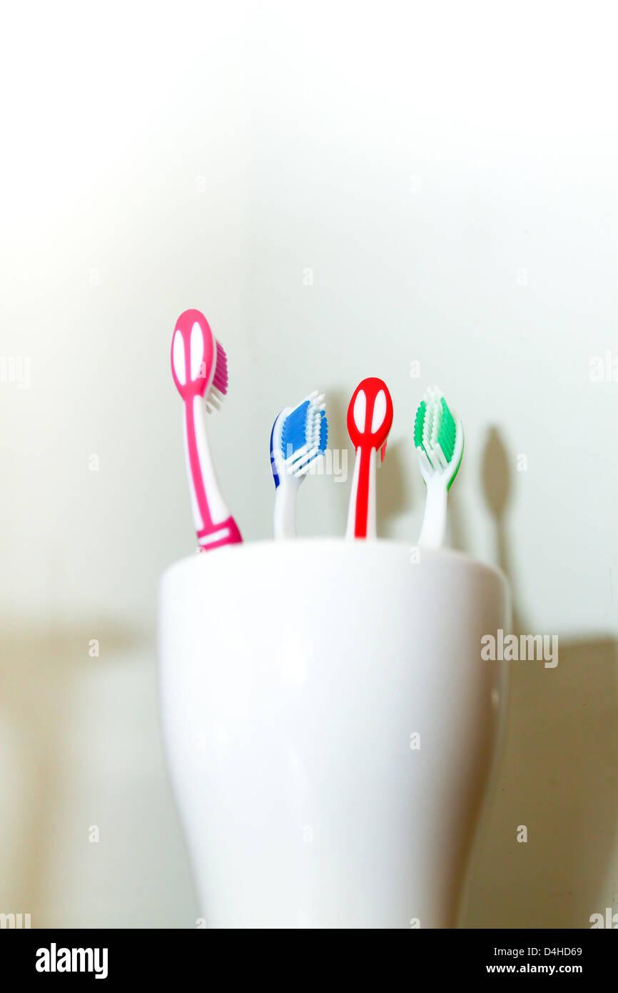 Quatre brosses à dents de couleur différente dans la tasse blanche Photo Stock