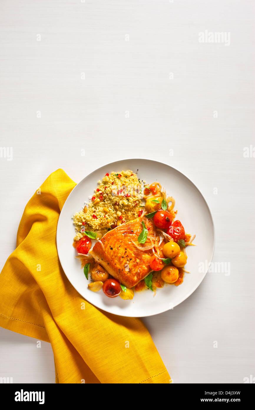 L'omble chevalier avec tomates cerises boursouflée, avec le poivron Couscous aux noix de pin Photo Stock