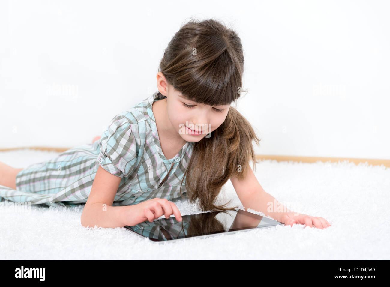 Petite fille jouant avec une tablette numérique moderne tout en se trouvant sur un tapis blanc dans une chambre Photo Stock