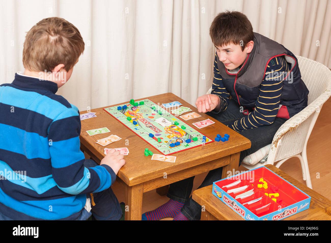Deux garçons ( frères ) jouer jeu de monopoly junior à la maison Banque D'Images