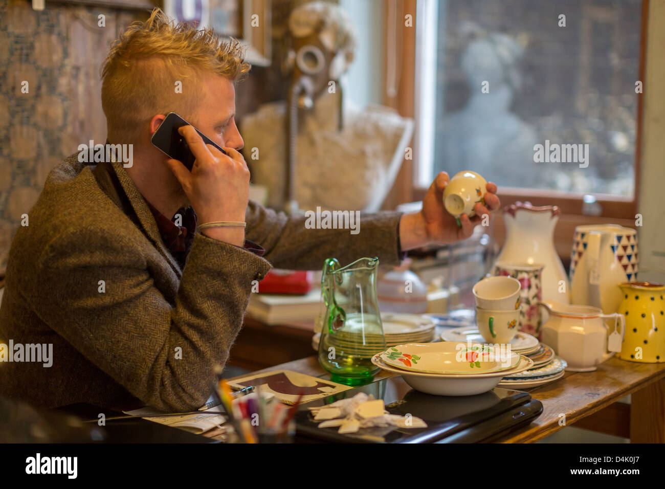 Man talking on cell phone at table Banque D'Images