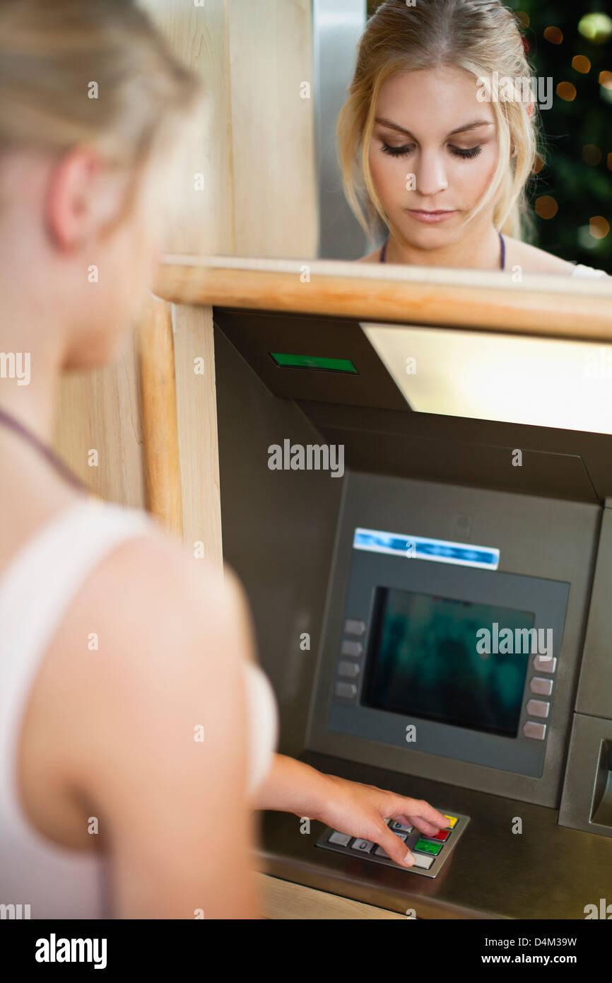Femme à l'aide du clavier sur ATM Banque D'Images