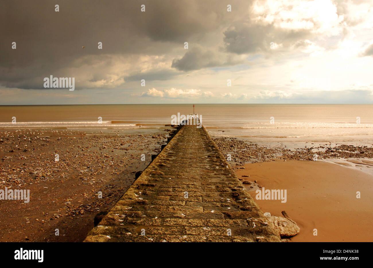 Scène de plage d'hiver - digue menant à des vagues - des lignes - tempête dramatique nuages menace. Photo Stock