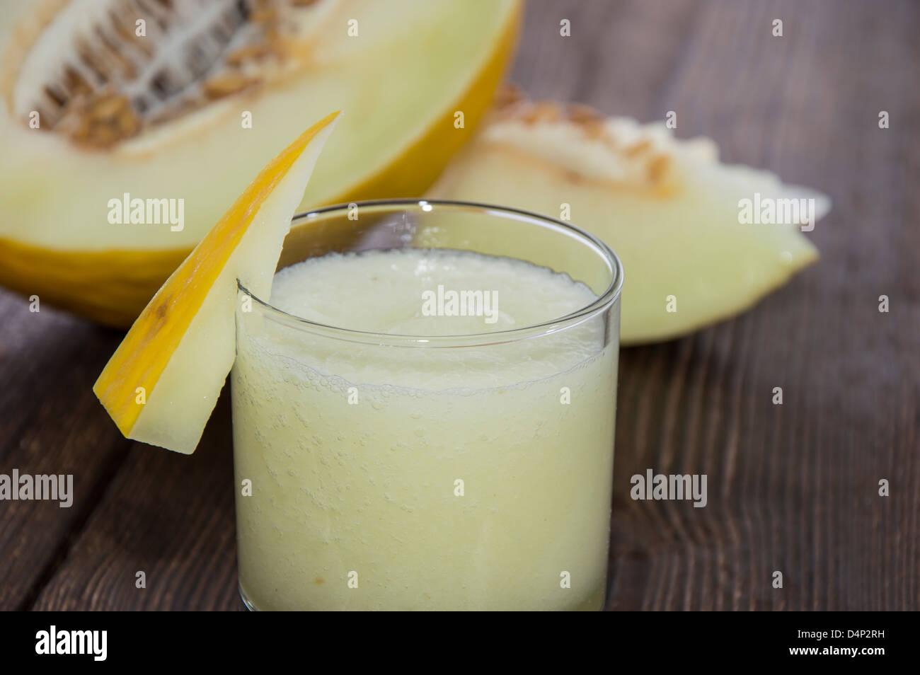 Fait frais Jus de miellat avec des morceaux de fruit sur fond de bois Photo Stock
