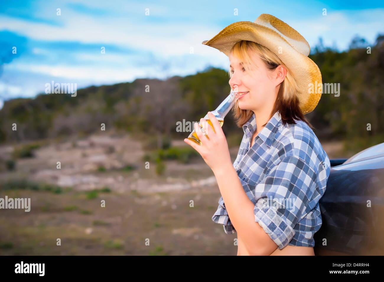 Portrait de country girl holding bouteille de bière, 19 femmes de race blanche, Texas, États-Unis Photo Stock