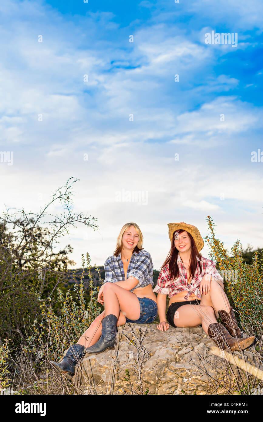 - Deux amis adolescents de sexe féminin dans une tenue de fille pays assis sur un rocher, les femelles 19 Caucase, Photo Stock