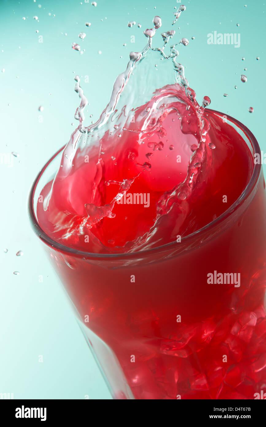Close up d'un splash sur un verre de jus de fraises Photo Stock