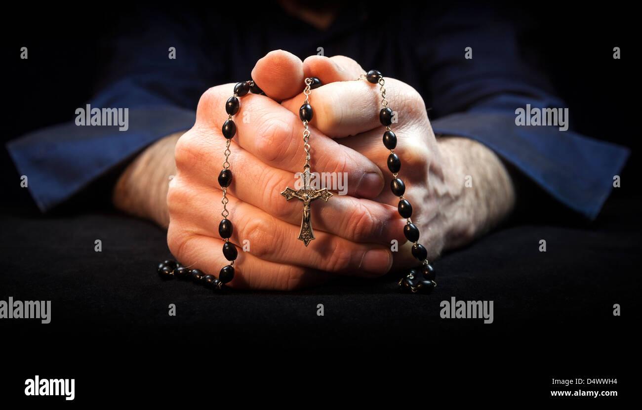 Hands holding rosary et traverser tout en priant. Photo Stock