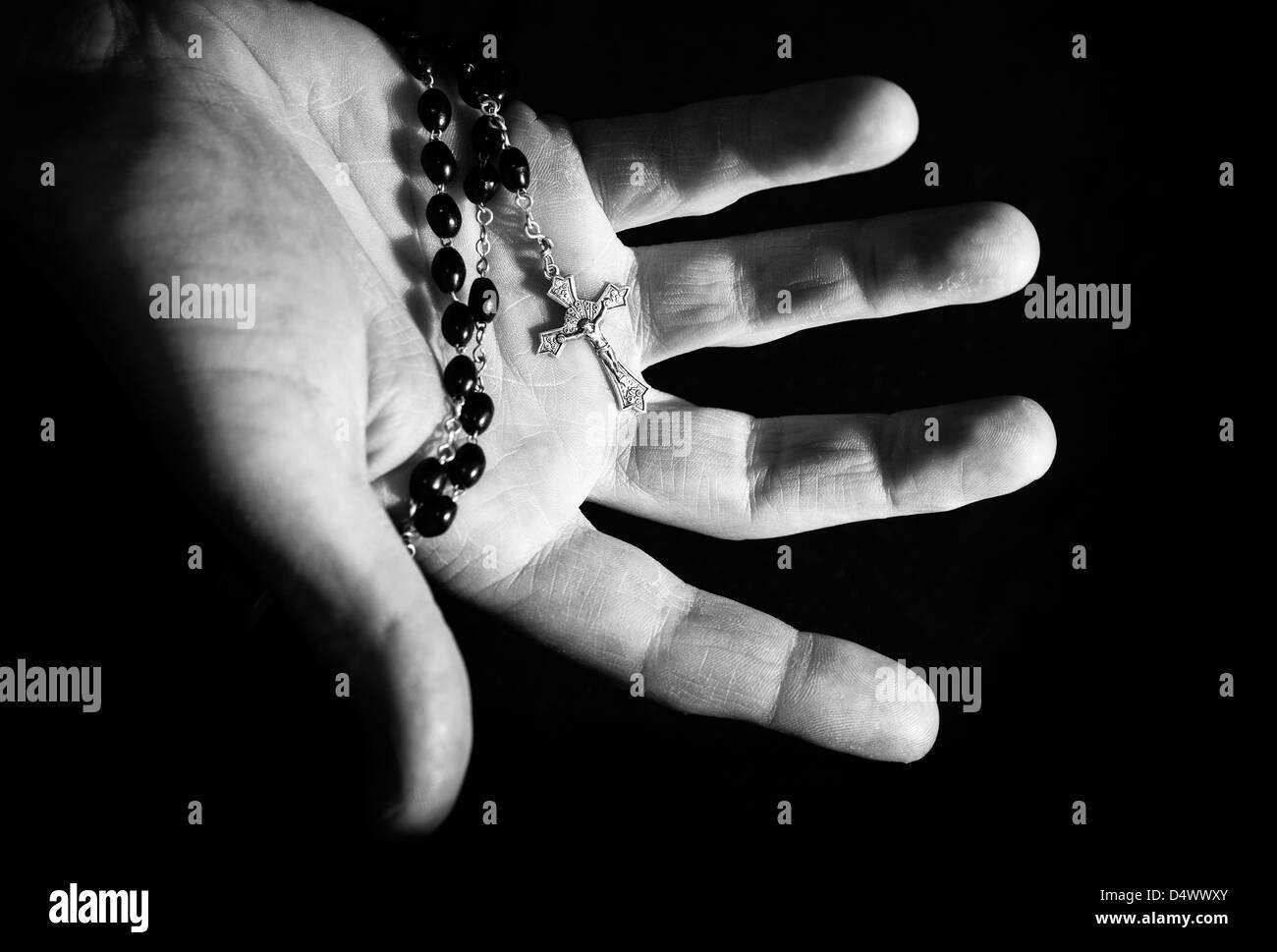 Coup de main tenant à chapelet et croix. Photo Stock
