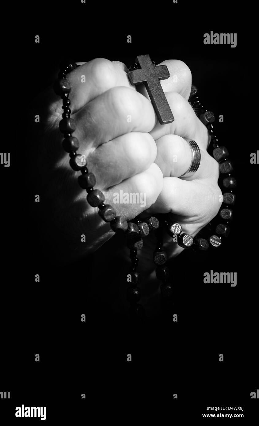 Mains tenant sur croix et chapelet en priant. Photo Stock
