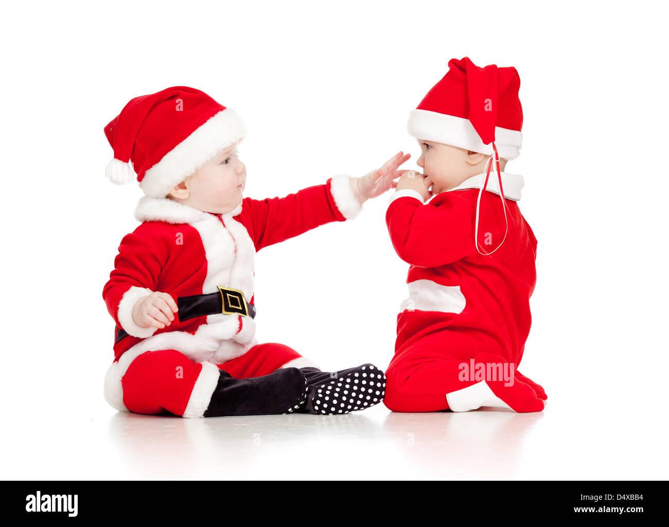 b11c723ccc48e Deux bébés drôles au Père Noël vêtements jouent ensemble isolé sur fond  blanc