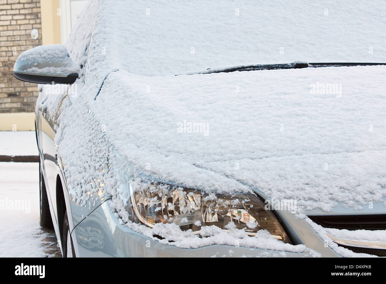 Capot avant et les phares de voiture européenne couverts d'une couche de neige fraîche au cours d'une saison d'hiver rigoureux Banque D'Images