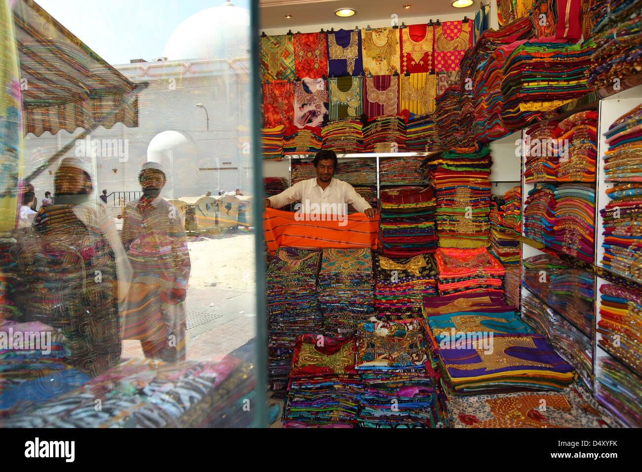 L'homme en tissu pliable boutique textile, Dubaï, Émirats Arabes Unis Photo Stock