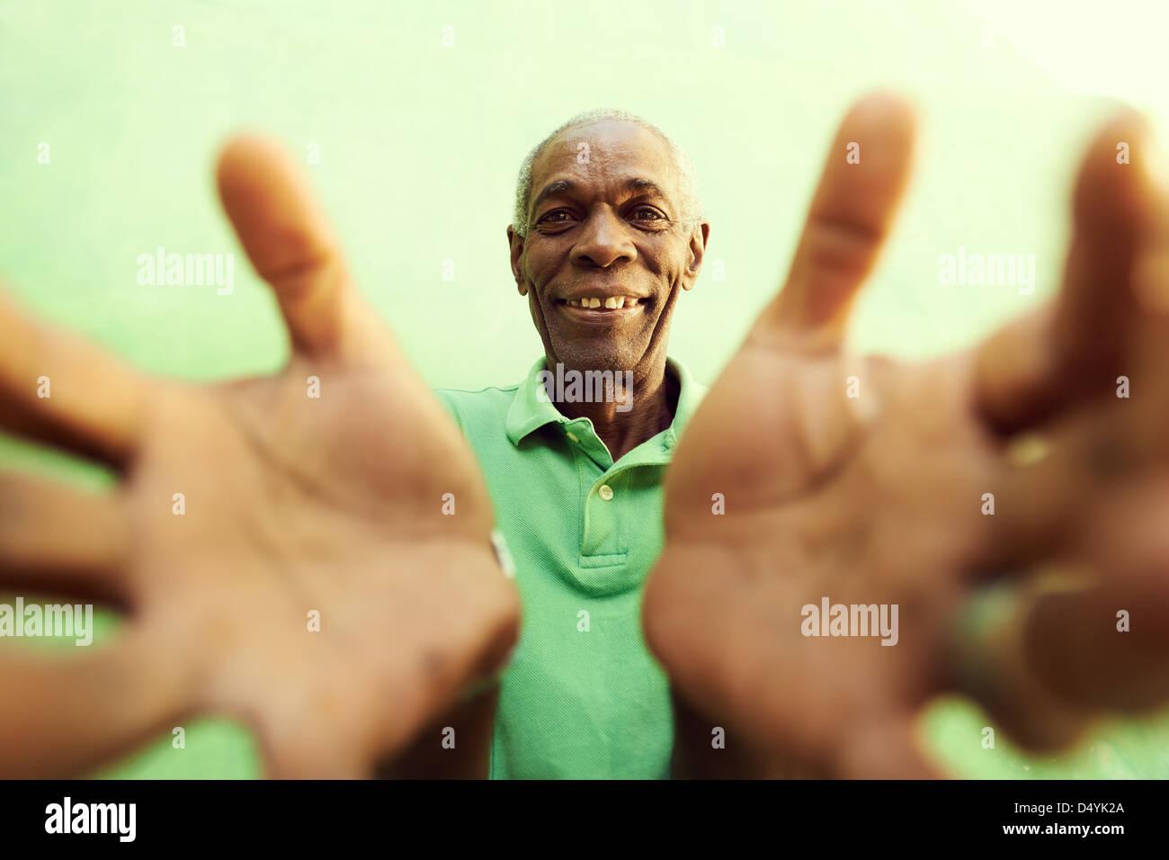 Portrait of senior homme noir avec les mains et les bras ouverts pointant sur appareil photo. Fond vert Photo Stock