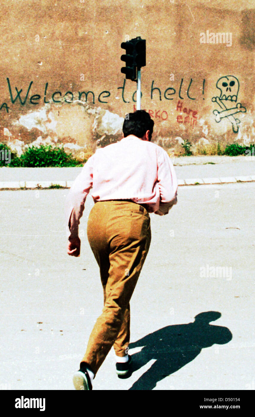 Un homme brave embusqués alors qu'il passe devant un graffiti scrawl qui lit 'Welcome to hell' Photo Stock
