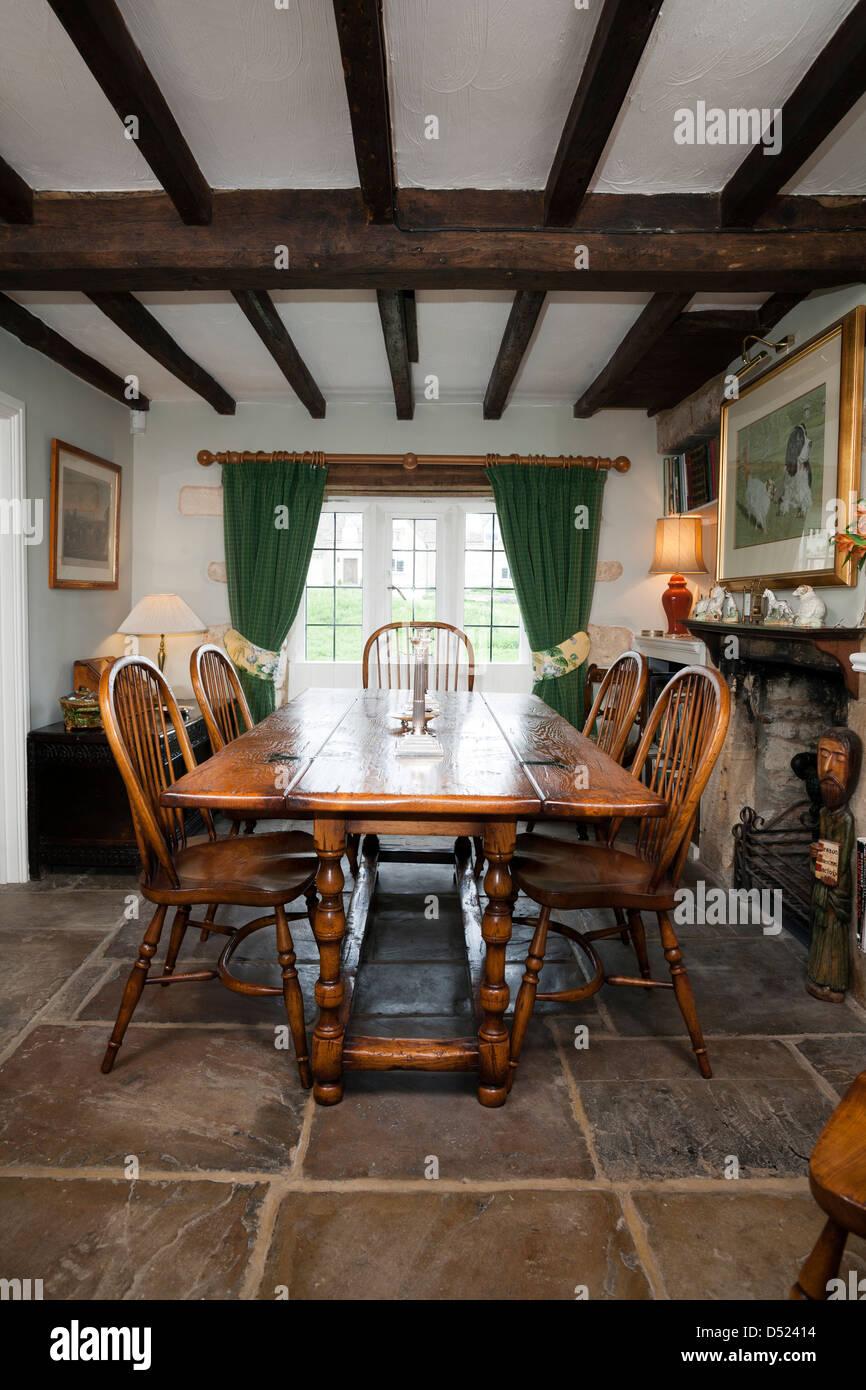 Une période cottage salle à manger avec plafond à poutres apparentes et un sol en pierre. Photo Stock