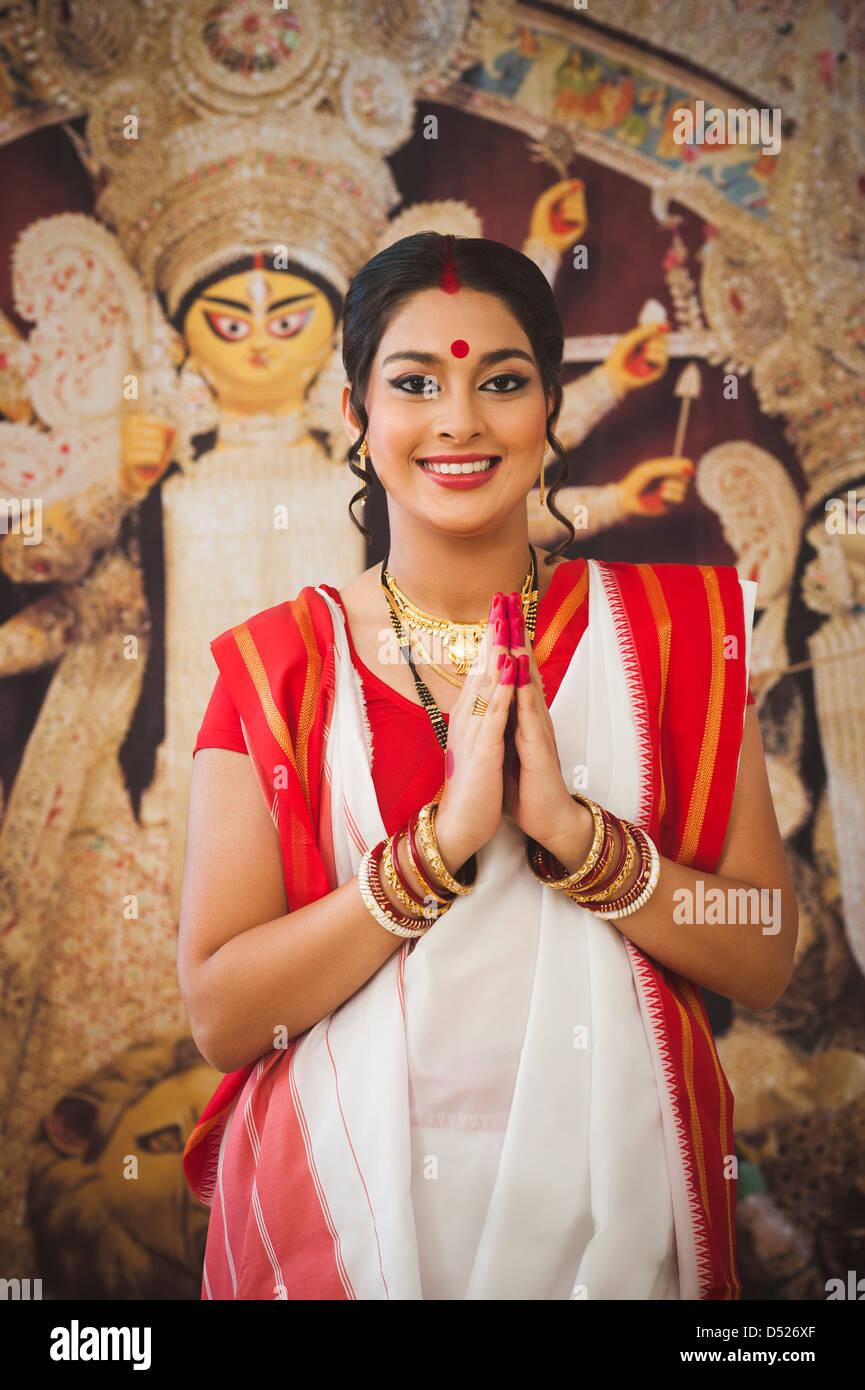 Bengali femme debout dans une position de prière à Durga Puja Banque D'Images