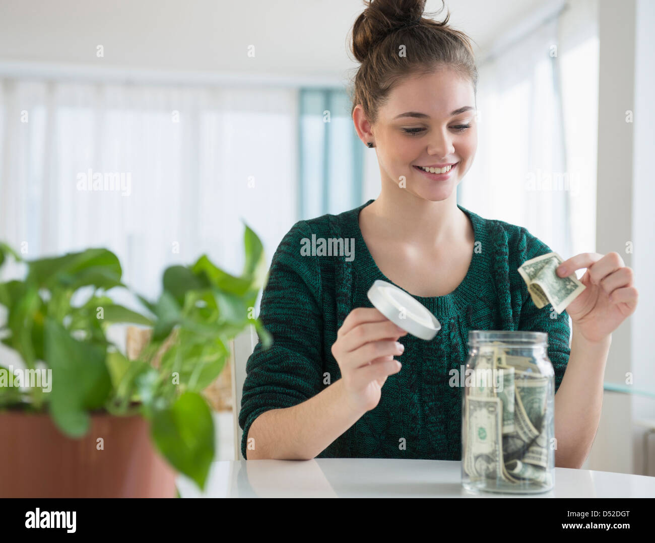 Woman putting money in savings jar Banque D'Images