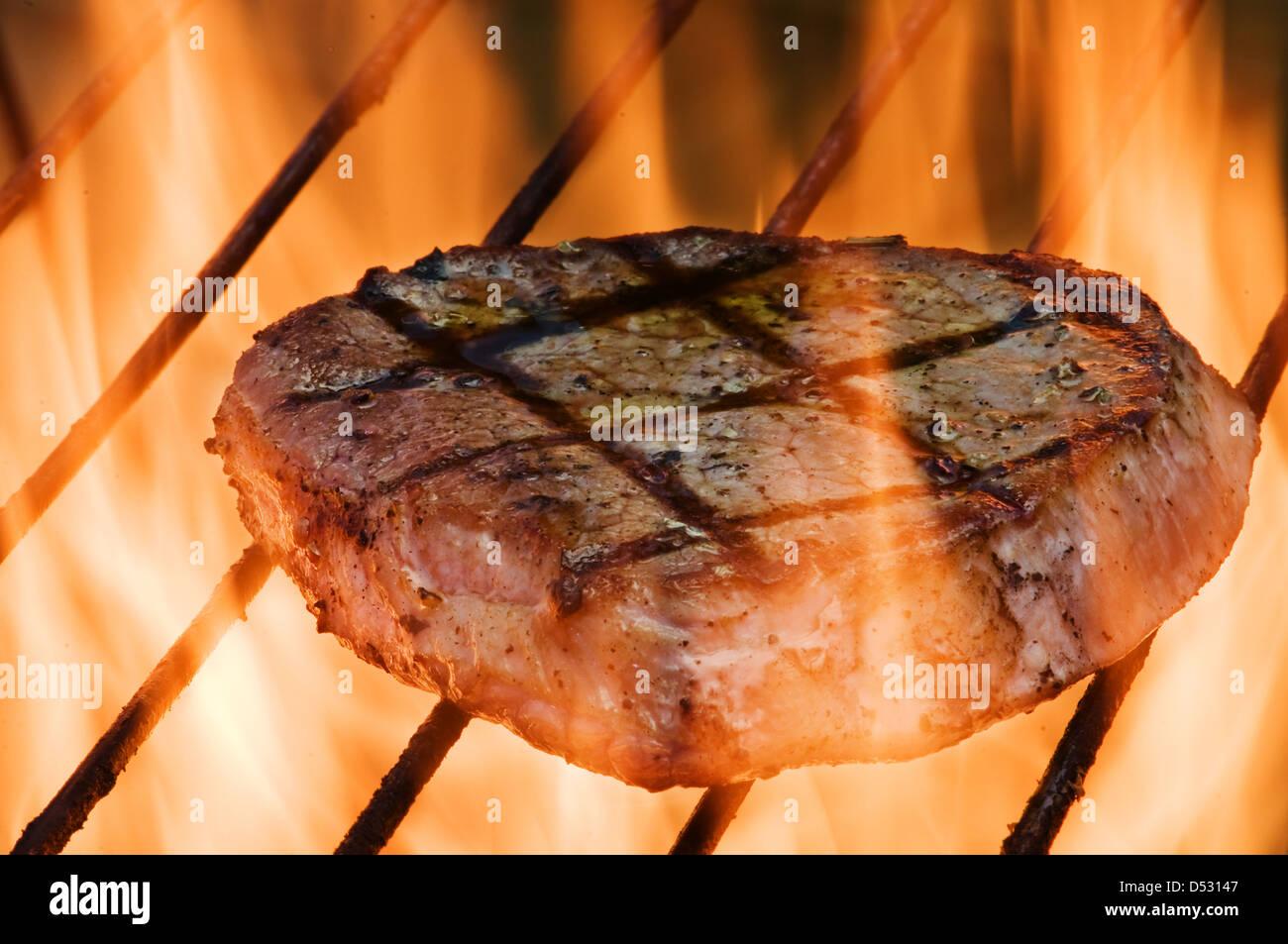 Le bifteck sur le grill bar rayé fiery closeup Photo Stock