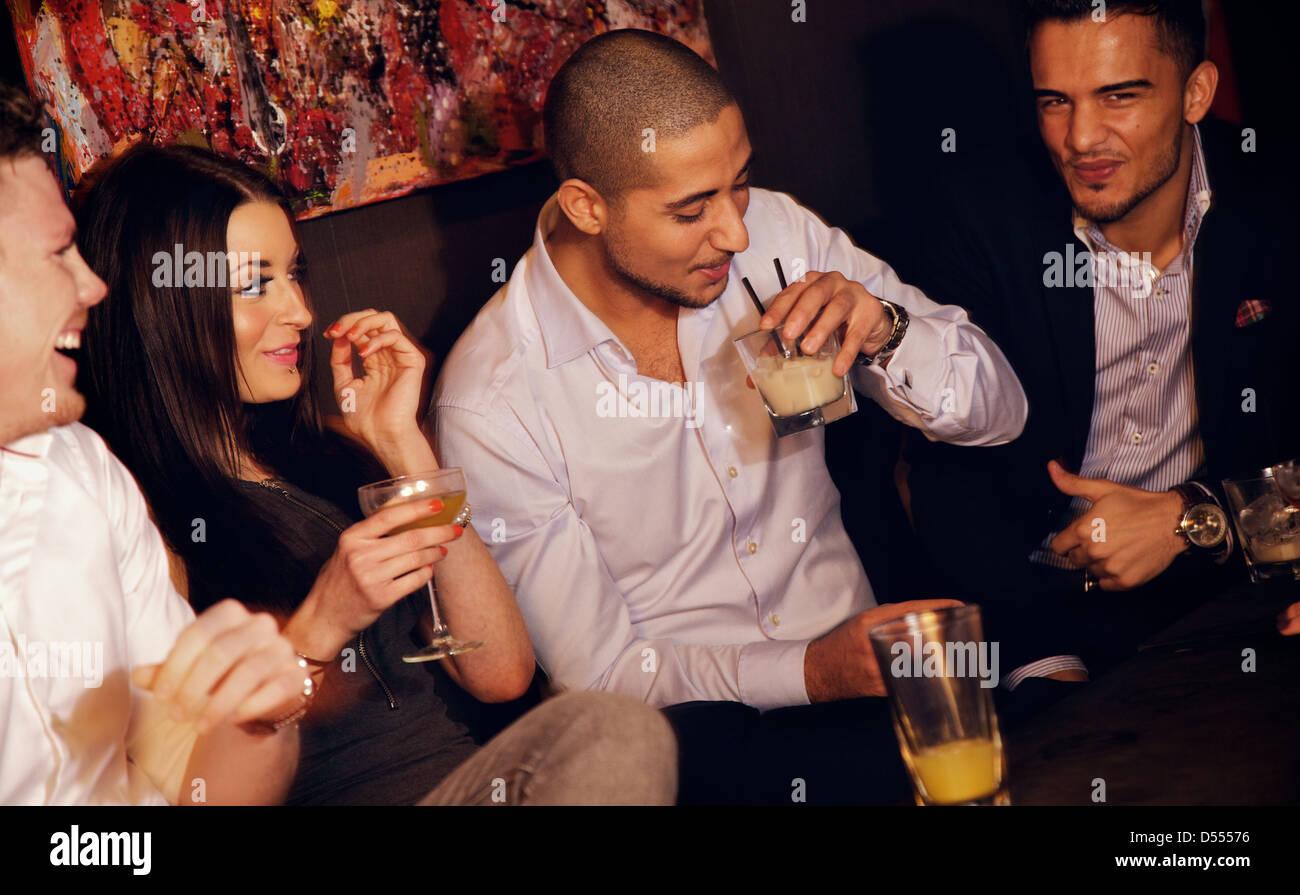 Groupe d'hommes de s'amuser ensemble avec leur jolie amie au bar Photo Stock