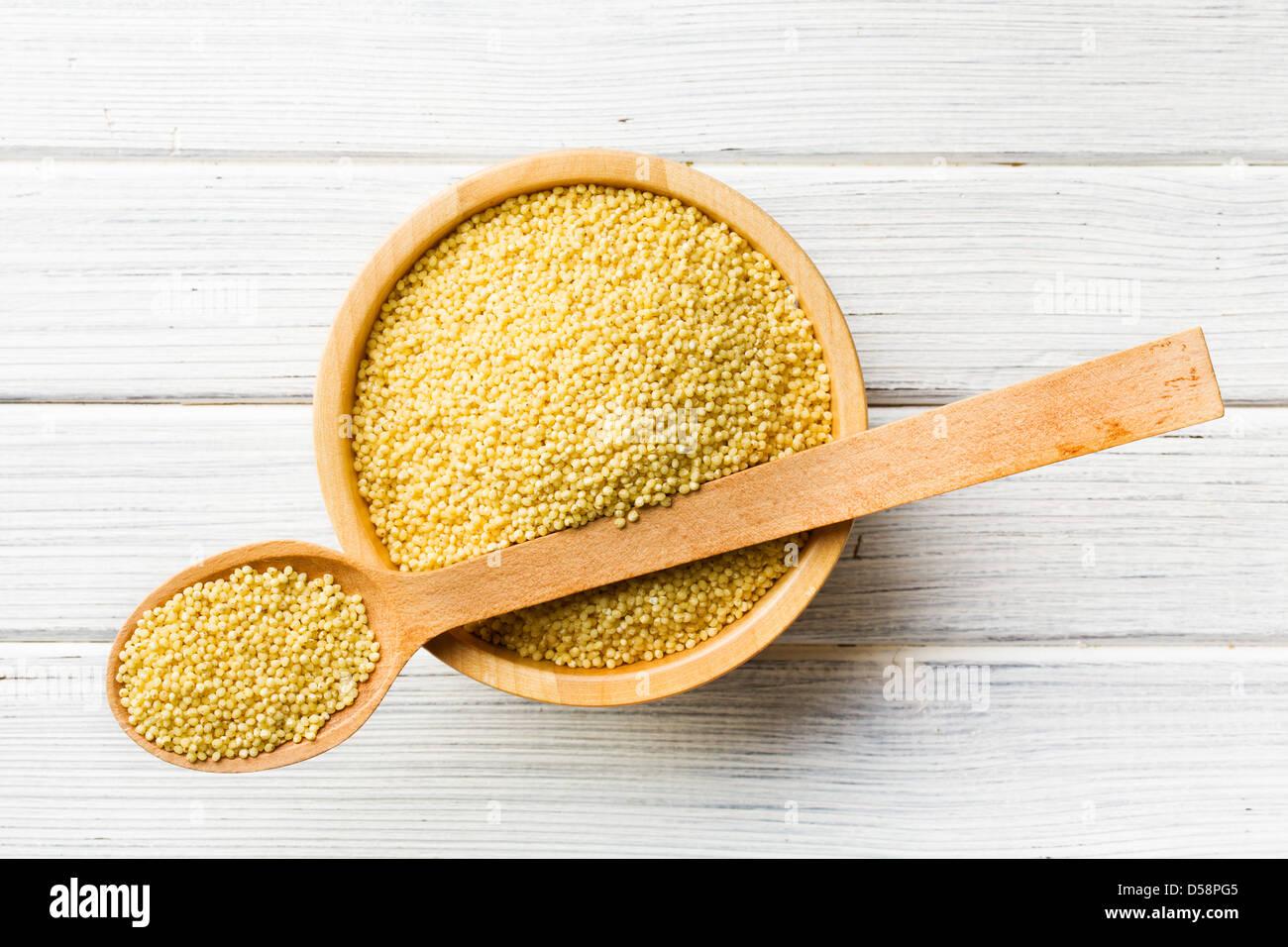 Le millet dans une cuillère en bois Photo Stock