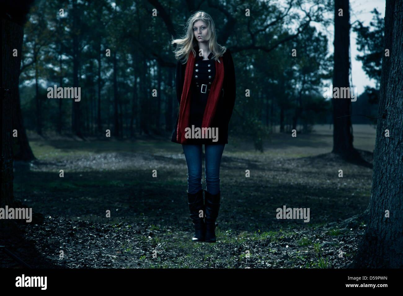 Femme blonde manteau noir écharpe rouge extérieur flottant woods ciel bleu Photo Stock